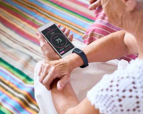 Senior woman measuring heart rate with smart phone